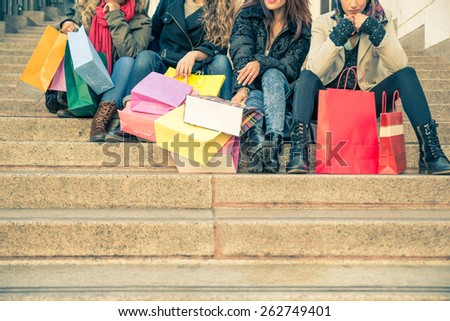 Women with shopping bags - Four girls sitting on staircase holding paper shopping bags - Concepts about shopping,women and lifestyle - stock photo