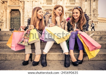 Women with shopping bags - Portrait of three pretty girls sitting on a staircase while laughing and talking - stock photo