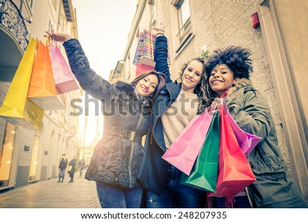 Women with shopping bags - Portrait of three pretty girls walking and looking at shops - Tourists buying clothes and presents - stock photo