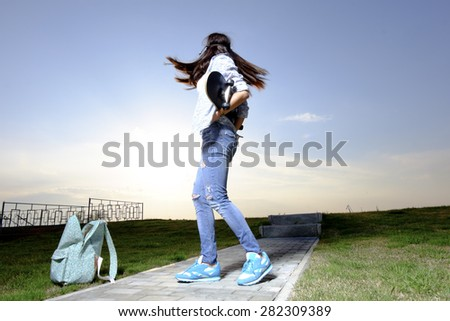 Women with skateboard in hands dancing against evening sky. Backpack on the ground. Beautiful fashionable young woman posing with skateboard. Hipster style of life. Toned with instagram style filter.