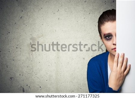 Women. Woman with bruises victim of domestic violence or accident hiding behind wall - stock photo