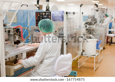 Women working at the pharmaceutical factory. Shallow DOFF. See more images and video from this series.  - stock photo