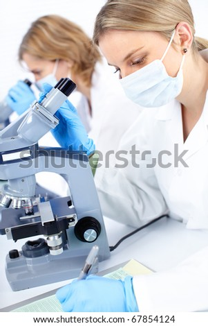 Women working with a microscope in a lab - stock photo