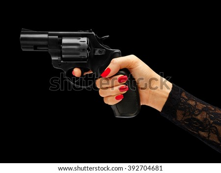 Womens hand aiming revolver gun isolated on black background. Business concept - stock photo