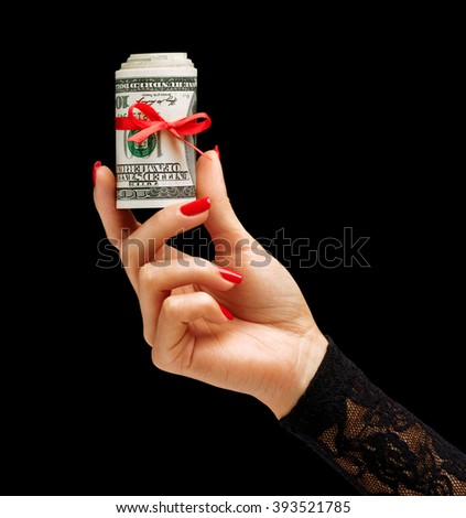 Womens Hand holding Money with red ribbon isolated on black background. Business concept - stock photo
