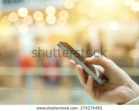 Womens hand using mobile phone on the bokeh background - stock photo