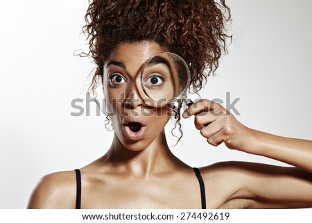 wondered woman with a one eye watching in magnifying glass - stock photo
