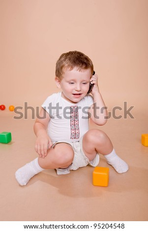 Wonderful baby talking on the cell phone. Isolated on beige