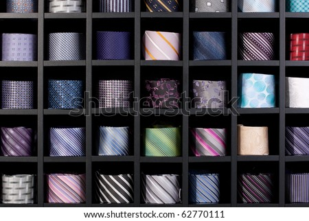 Wonderful background shot of a multi-coloured collection of rolled-up ties, in a retail setting.