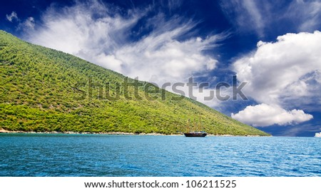 Wonderful brown yacht swimming in turquoise Aegean sea. - stock photo