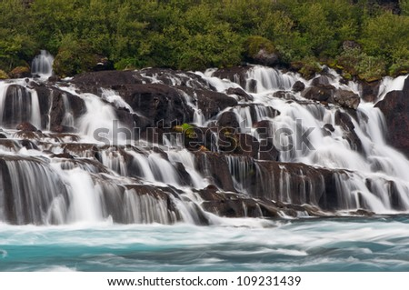 wonderful cascade Hraunfossar waterfalls with green water in iceland - stock photo