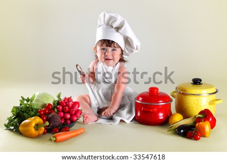 Wonderful child cook in surroundings vegetables and kitchen utensils - stock photo