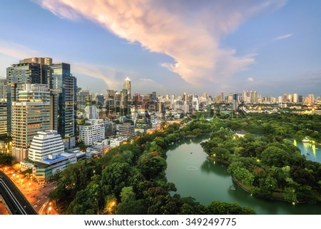 Wonderful evening period cityscape at Lumphini Park, Bangkok, Thailand. Lumphini Park (or Lumpini Park) is a park in Bangkok, Thailand. The cloud is orange.  - stock photo