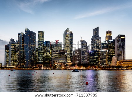 Wonderful evening view of Marina Bay and downtown of Singapore. Scenic skyscrapers and other modern buildings are visible on blue sky background. Singapore is a popular tourist destination of Asia.