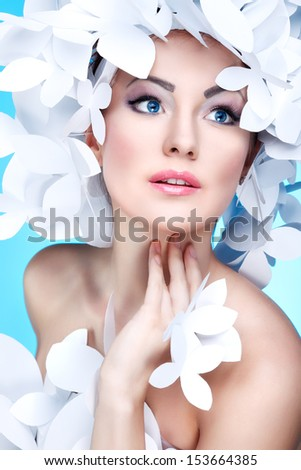 Wonderful girl in a hat from paper white butterflies. On a blue background. Beauty Face - stock photo