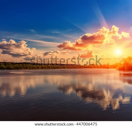 Wonderful landscape. Majestic Sunset. the overcast sky, clouds over the water. Dramatic, beautiful scene in the evening on the lake in the woods. Beauty in the world.   Instagram toning effect. - stock photo