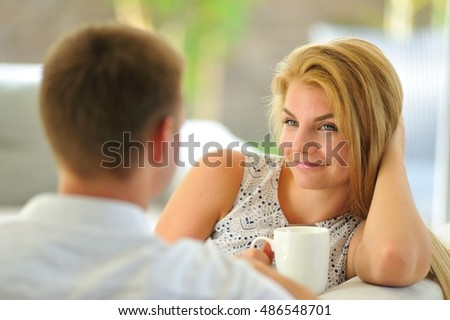 Wonderful long-haired young blonde woman sitting on a couch propped her head with one hand and holding a mug of delicious tea in another hand, in love looking at her husband
