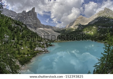 Wonderful mountain lake azure color with vegetation and peaks.