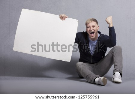 Wonderful news: Overjoyed laughing man holding white blank signboard with space for text isolated on grey background. - stock photo