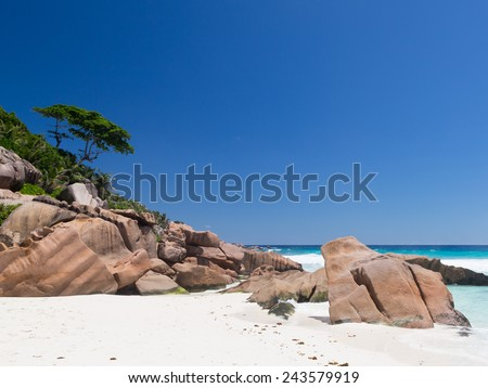 wonderful scenic sea beach with big rocks and trees and clear skies in the Seychelles - stock photo