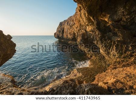 Wonderful sea landscape. Rocky shore calm sunny morning.  - stock photo