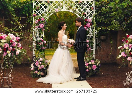 wonderful stylish rich happy bride and groom holding hands at a wedding ceremony look at each other in green garden near white arch with flowers Rome Italy  - stock photo