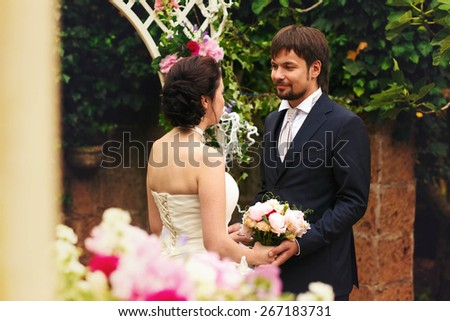 wonderful stylish rich happy bride and groom holding hands at a wedding ceremony look at each other in green garden near white arch with flowers Rome Italy