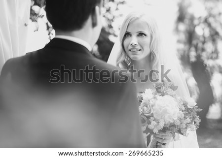 wonderful stylish rich happy bride and groom holding hands look et each other at a wedding ceremony in  garden near arch with flowers - stock photo