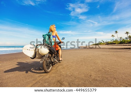 wonderful trip - woman riding a motorcycle with the surfboard - stock photo