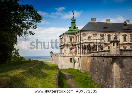 Wonderful view of beautiful ancient castle with castle moat and summer nature