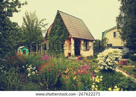 wonderful vintage rustic country house in the lush garden. garden flowers - stock photo