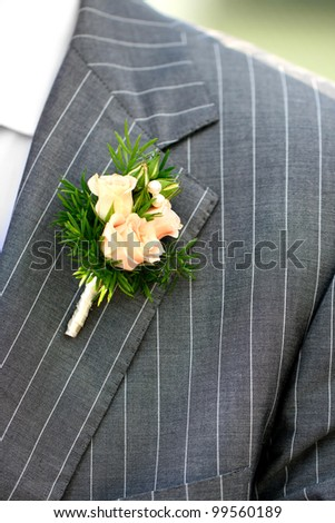 Wonderful wedding boutonniere on a costume of groom from beautiful colorful flowers. - stock photo
