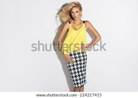 Wonderful young blonde woman in fashionable clothes with long wavy hair looking at camera - stock photo