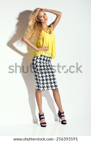 Wonderful young blonde woman in fashionable summer clothes with long wavy hair looking at camera, high heels shoes - stock photo