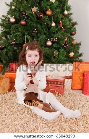 Wondering little girl in a front of Christmas-tree - stock photo