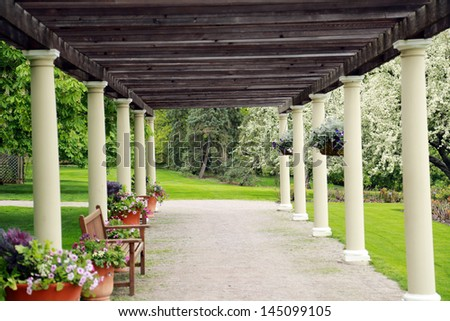 wood and pillar pergola with flowers and benches