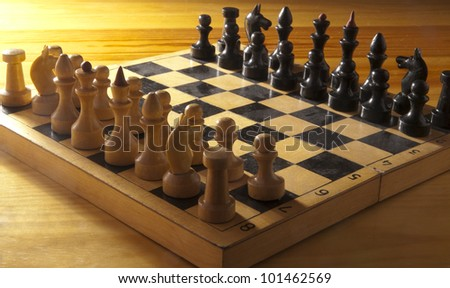 wood and plastic figures on a chess board on wooden table - stock photo