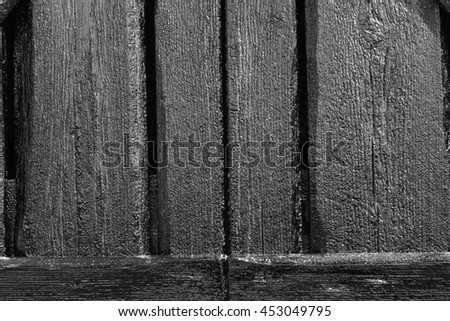 Wood and tar texture on some plank. Black wooden wall in bright sunshine. Recently tarred. BW, HDR-toning. - stock photo