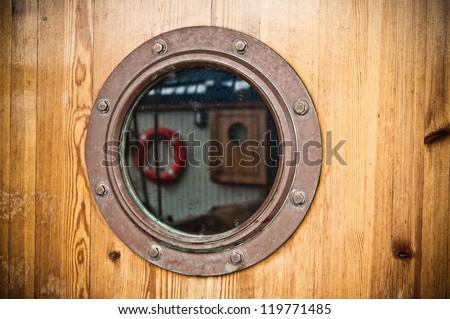 wood background and nautical porthole, close-up - stock photo