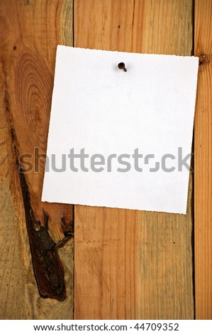wood background, white note paper, vertical