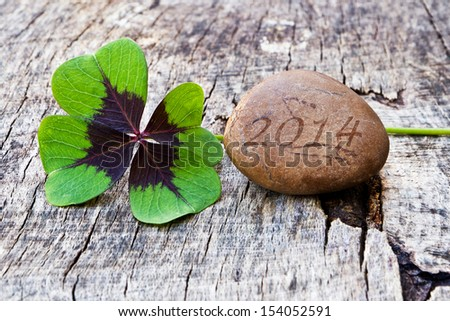 Wood background with four leaf clover and stone, 2014 - stock photo