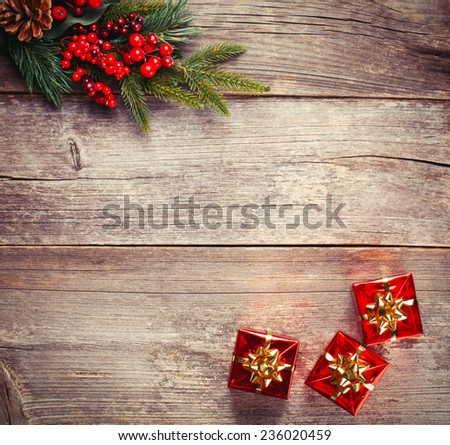 Wood background with pine branch and red gifts