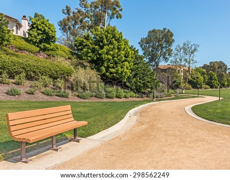 Wood bench and winding park road. Peaceful empty dirt walking path through green grass and hillside in sunny suburban park. Clear blue sky.   - stock photo