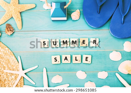 Wood Blocks on Light Blue Table with Sea Shells, Starfish, Beach Hat and Slippers for Summer Sale Concept - stock photo