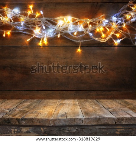 wood board table in front of Christmas warm gold garland lights on wooden rustic background. filtered image. selective focus  - stock photo