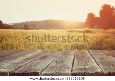 wood board table in front of field of wheat on sunset light. Ready for product display montages  - stock photo