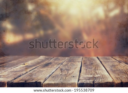 wood board table in front of summer landscape with lens flare.  - stock photo