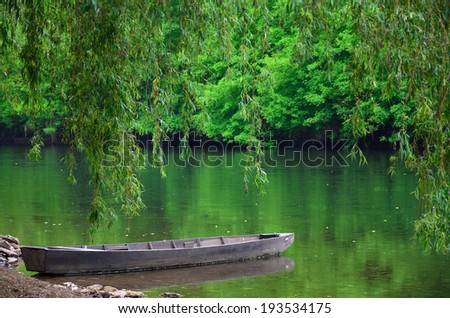Wood boat is landing near the shore of the pond. Lush foliage are reflected in the calm water surface. - stock photo