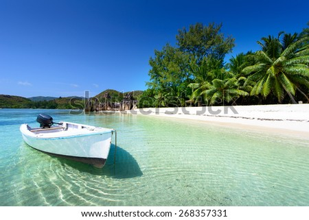 wood boat on the beach with palms - stock photo