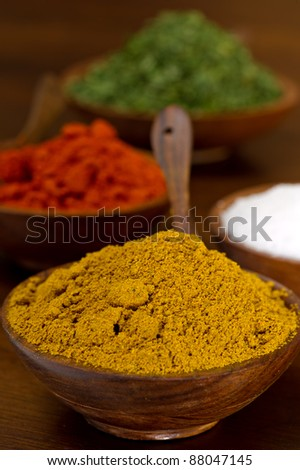 Wood bowls filled with colorful spices - curry, paprika, salt and parsley flakes.  Each bowl has a wood spoon and are shot on a wood table.